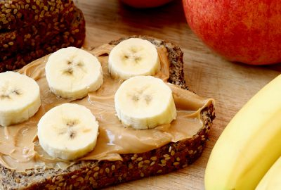 toasted bread with peanut butter and cut up bananas. With bread, an apple and bananas in the background