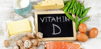 Vitamin D on a chalkboard surrounded by snap peas, eggs, salmon, mushrooms, butter, milk and cheese.