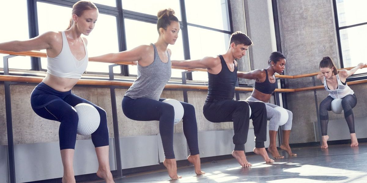 Barre group training class. 5 athletes performing chair sits on tip toes with a ball heald between their knees holding onto the bar behind their backs.