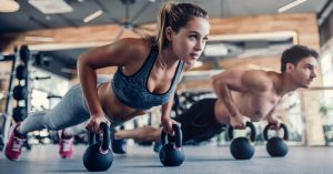 Personal Fitness Workout With kettlebells. A women and a Man in Pushup plank using kettle bells for support.